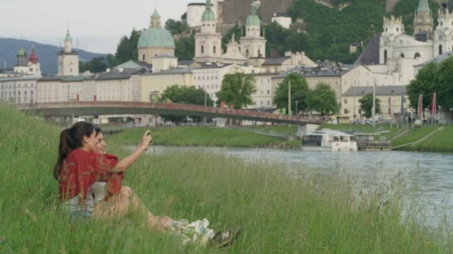 Wide shot of women sitting near river examining photographing on cell phone / Salzburg, Austria