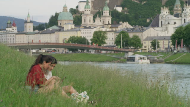 Wide shot of women sitting near river examining photographs on cell phone / Salzburg, Austria