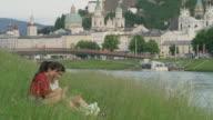 Wide shot of women sitting near river examining photographs on cell phone / Salzburg, Austria