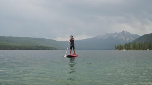 Wide shot of young man paddleboarding on lake / Redfish Lake, Idaho, United States
