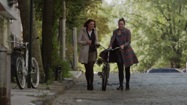 Wide shot of young women walking with bicycle on cobblestone street / New York City, New York, United States
