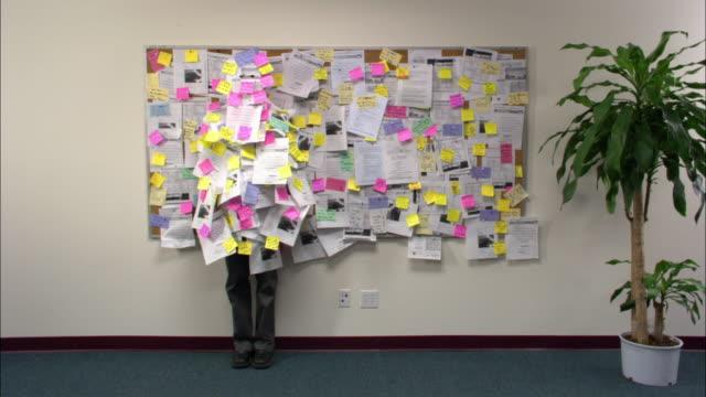 Wide shot office employee camouflaged against bulletin board / boss walking by / employee walking away / low angle