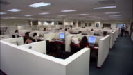 Wide shot office workers working in cubicles and empty cubicles on office floor / Los Angeles, California