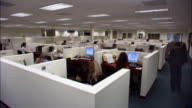 Wide shot office workers working in cubicles / dissolve throughout day to last worker turning off light/ low angle