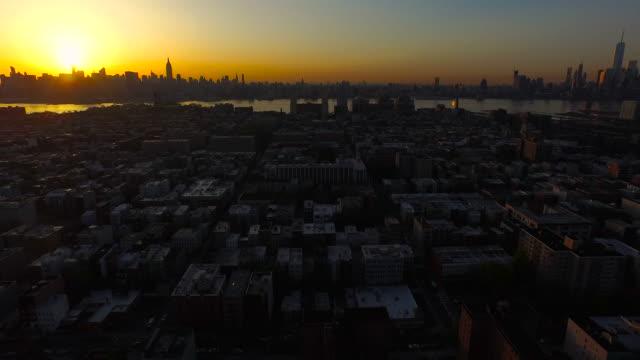 Wide shot over Hobken moving toward NYC skyline over Hoboken at sunrise