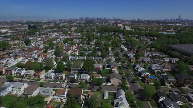 Wide shot over New Jersey suburb, moving toward New York City skyline on horizon