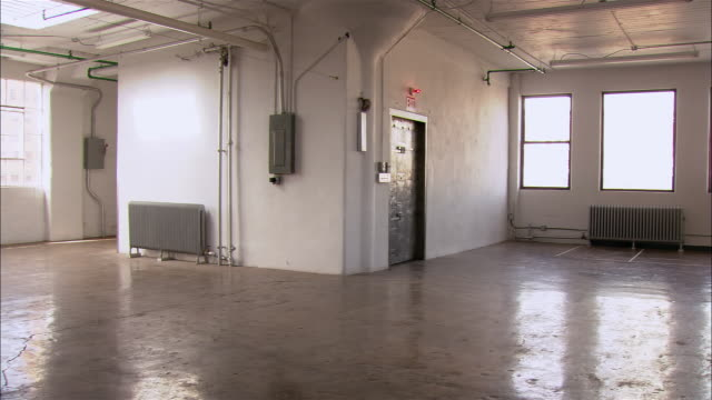 Wide shot pan across empty loft space with sunlight coming through windows and bicycle leaning against wall/ Brooklyn, New York