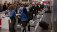 Wide shot pan behind ticket counter with agents putting luggage on conveyer belt /Hartsfield Airport, Atlanta