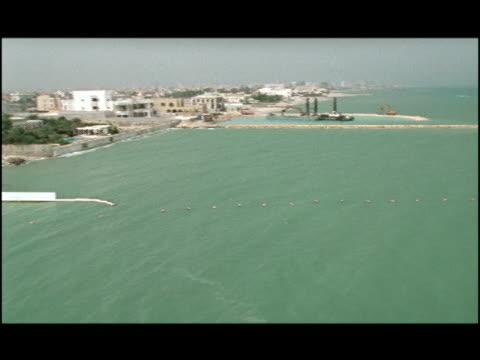 2001 Wide shot pan Buildings and bulldozers lining coast of Persian Gulf beach/ Kuwait City, Kuwait