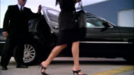 Wide shot pan Businesswoman exiting chauffeur-driven luxury car and greeted by pilot at door of private jet at Opa Locka Airport/ Miami, Florida, USA