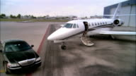 Wide shot pan Businesswoman exiting private jet and entering chauffeur-driven luxury car at Opa Locka Airport/ Miami, Florida, USA
