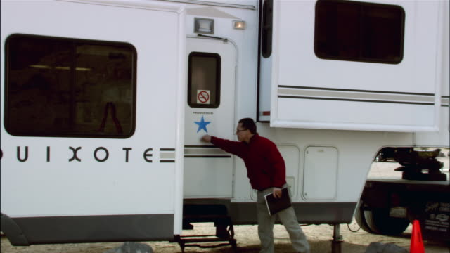 Wide shot pan dolly shot man walking to trailer and knocking on door / actress dressed in Ancient Rome period costume exiting trailer talking on cell phone / taking script and water from crew / being ushured to set by director / Red Rock Canyon State Park