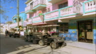 Wide shot pan dune buggies parked on street outside ice cream shop in downtown Belize City, Belize