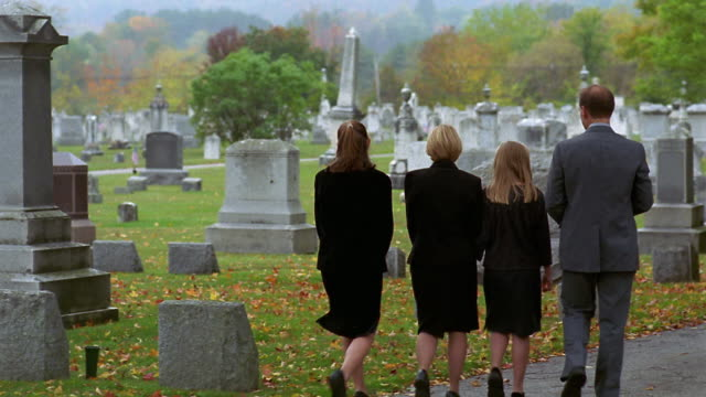 Wide shot pan family visiting grave and putting flowers next to it / Vermont