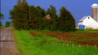 Wide shot pan from country road to farm with silos / Iowa