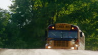 Wide shot pan from mailboxes to school bus picking up children on country road / Vermont