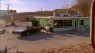 Wide shot pan from sign to young people getting out of convertible and entering roadside diner