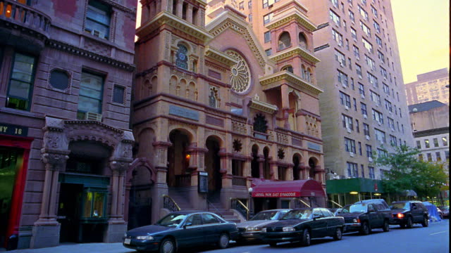 Wide shot pan from synagogue to fire station on Upper East Side of Manhattan / New York City