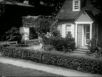 1954 Wide shot pan girl running out of house, dropping something while running across lawn, picking it up, and running down sidewalk / AUDIO