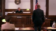 Wide shot pan lawyer rising, taking transcripts from court reporter to defendant