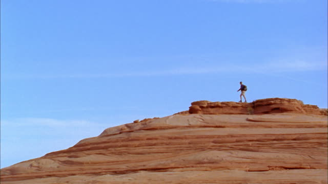 Wide shot pan man hiking along desert mesa