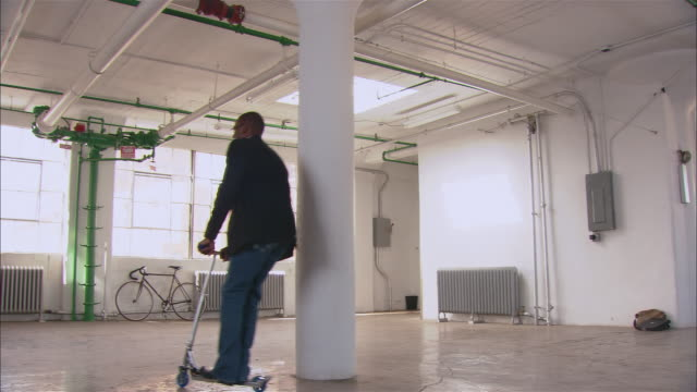 Wide shot pan man riding push scooter in empty loft space/ Brooklyn, New York