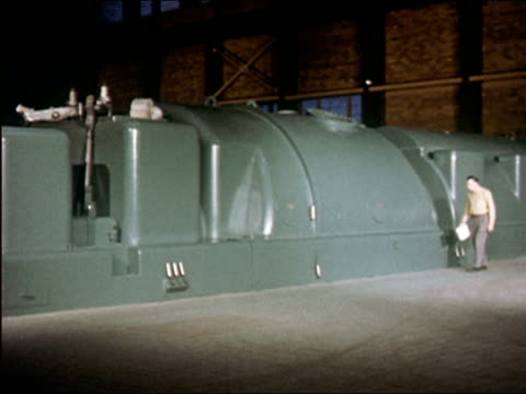 1957 wide shot pan man walking along and taking readings from large green generator