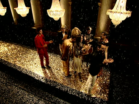 Wide shot pan Models parading down catwalk and applauding below chandeliers during finale of B&C European Style fashion show rehearsal/ Belgrade, Serbia