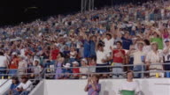1985 Wide shot pan Orlando Renegades football fans cheering in bleachers / Orlando, Florida, USA
