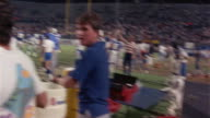 1985 Wide shot pan Orlando Renegades football players celebrating on field after game against Tampa Bay Bandits / Orlando, Florida, USA