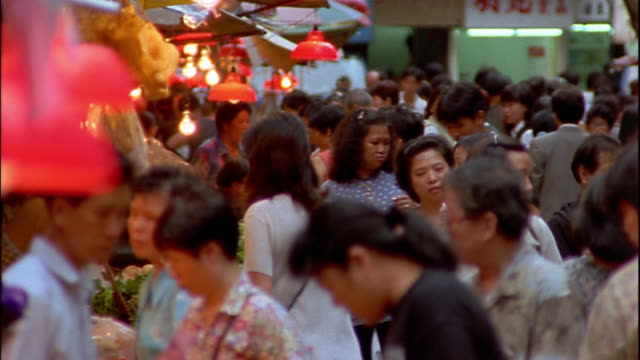 Wide shot pan people walking in crowded outdoor market / Hong Kong