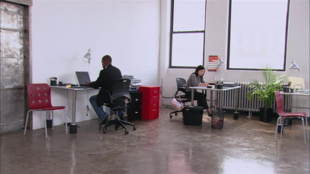 Wide shot pan people working at desks in loft office/ woman walking in while text messaging as man reads in reception area/ Brooklyn, New York