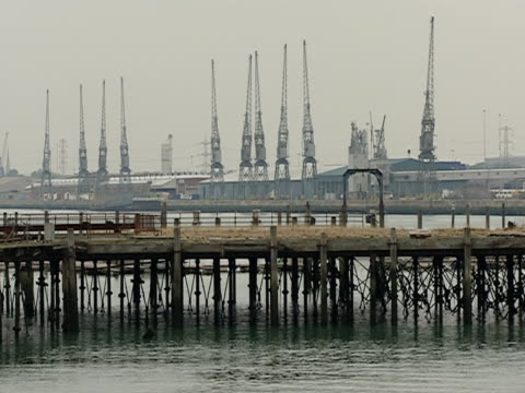 2003 Wide shot pan Pier crossing English Channel near cranes and buoy/ Southampton, Hampshire, England
