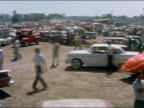 1959 wide shot pan raceway parking lot with teens hanging out in cars and pickup trucks