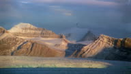 Wide shot pan snow-covered mountains at sunset / birds flying in sky / water in foreground / Arctic