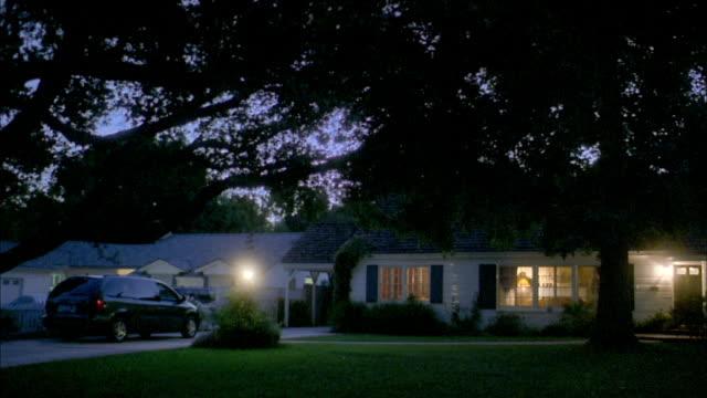 Wide shot pan suburban house and yard at night