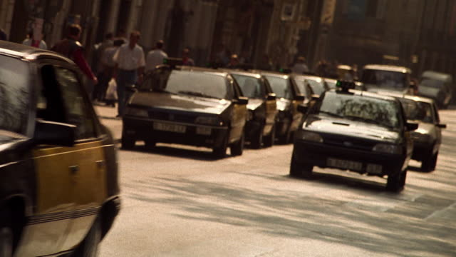Wide shot pan taxis and other traffic on city street