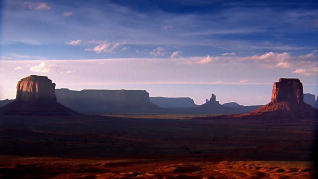 Wide shot pan time lapse clouds over Monument Valley