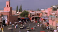 Wide shot pan time lapse people and traffic moving through city square / Marrakesh, Morocco