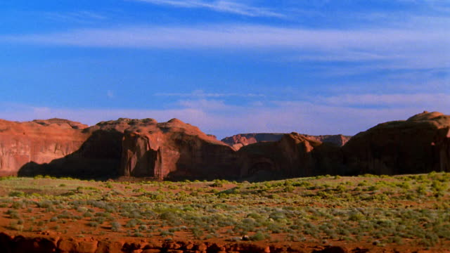 Wide shot pan time lapse rock formations with valley in foreground / Monument Valley