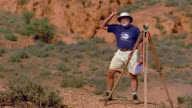 Wide shot pan to archaeologist with surveyor's level in desert / Australia