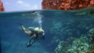 Wide shot pan woman scuba diving over coral reef with rock formation above water