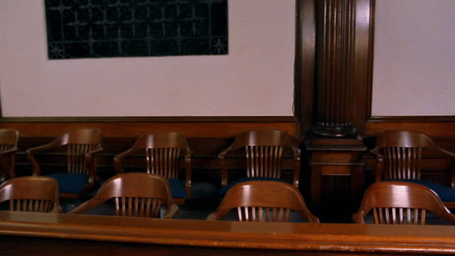 Wide shot pan wooden chairs in empty jury box in courtroom