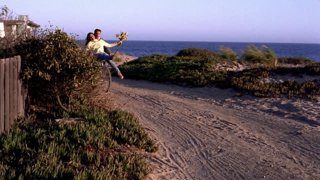 Wide shot pan young couple riding on bicycle by beach with woman on front holding flowers / California