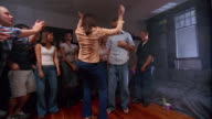 Wide shot pan young woman inviting man on sofa to dance at party, man hesitates then dances energetically