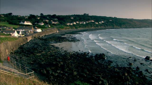Wide Shot pan-left - Gentle waves ripple ashore where a few quaint homes line the coast. / Cornwall, UK