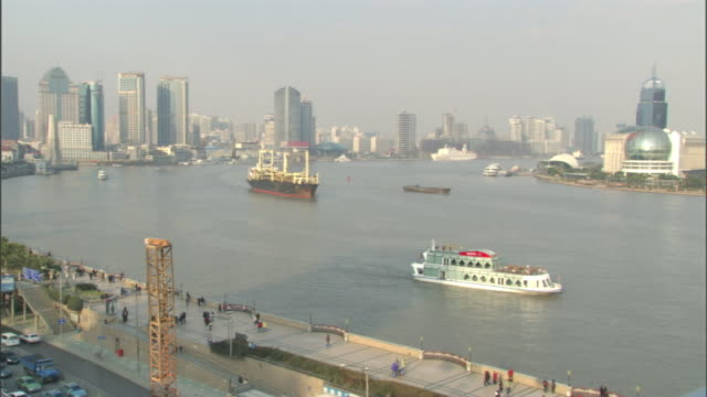 Wide Shot pan-left - Ships and traffic travel past the Pudong district of Shanghai, China. / Shanghai, China