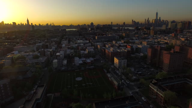 Wide shot panning right over Hoboken with NYC skyscrapers in distance at sunrise