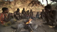 Wide Shot pan-right - Members of the Hadza tribe peel and eat bananas around a campfire in Tanzania. / Tanzania