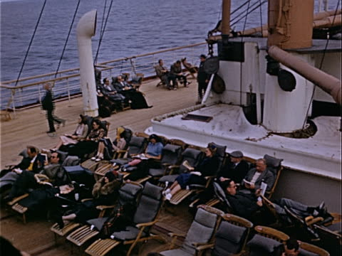 1939 Wide shot Passengers sitting in lounge chairs and walking on deck of vintage steamship during cruise in Atlantic Ocean / USA